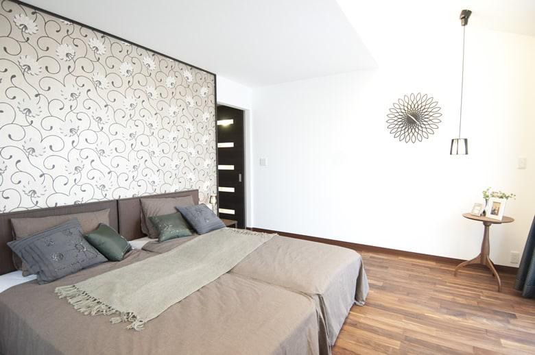 バルコニーから降り注ぐ光が、部屋全体を明るくしてくれる主寝室。高級感あるフローリングと印象的な壁のデザインが個性を主張しています。