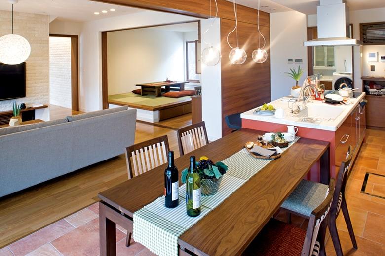 赤いキッチンが印象的なダイニングキッチンスペース。壁とテーブルの木調を合わせることで、全体的にシックであたたかな雰囲気にまとめています。インテリアや照明なども家づくりの参考になります。