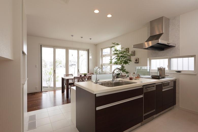 気持ちのいいほどにスタイリッシュで効率的なキッチンです。白い床タイルとキッチンのダークブラウンのコントラストもおしゃれ。