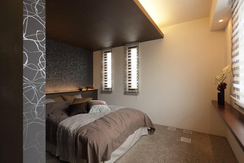 個性的なブラックグレーベースの壁と印象的な天井照明が不思議と安らぎを与えてくれる主寝室。