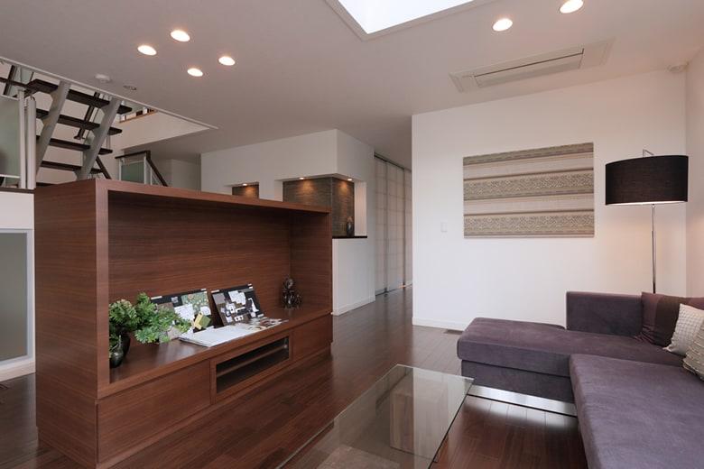 吹き抜けとオープン階段の存在が空間に奥行き感を感じさせるリビングスペース。床材と同系色の家具が、白い壁とコントラストを織りなし、心地よい空間を作っています。
