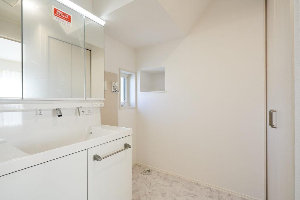 白基調で清潔感溢れる洗面室です。手前側には収納もあります。