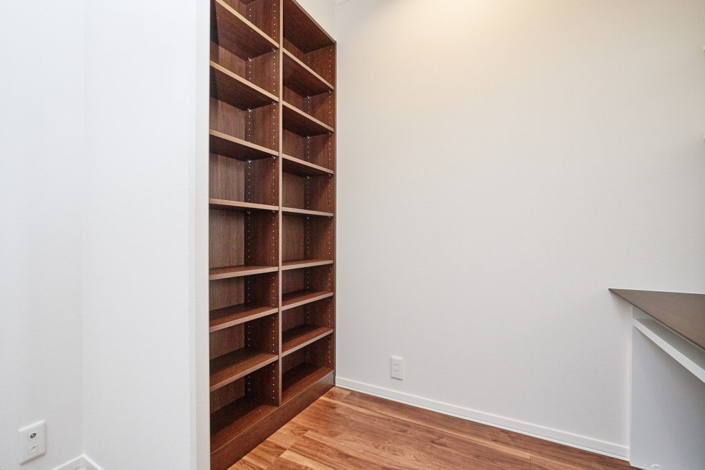 書斎デスクの背面に壁埋込型書棚も備え付けています。